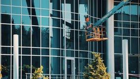 El limpiador de cristal del trabajador en una elevación hidráulica lava ventanas en el edificio de centro del rascacielos de la o metrajes