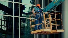 El limpiador de cristal del trabajador en una elevación hidráulica lava ventanas en el edificio de centro del rascacielos de la o almacen de video