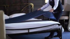 El limpiador del hotel hace una cama matrimonial en una habitación pequeña, acogedora Cámara lenta metrajes