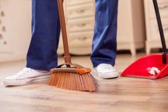 El limpiador masculino joven experto está limpiando el piso adentro Foto de archivo