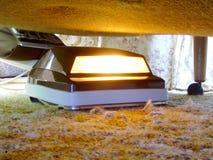 El limpiar con la aspiradora bajo la cama. Fotos de archivo