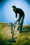El limpiar con la aspiradora del hombre joven Imagen de archivo