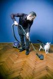 El limpiar con la aspiradora del hombre, mirando el gato Fotografía de archivo
