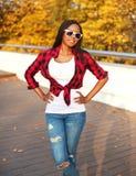 El llevar africano sonriente hermoso de la mujer del retrato gafas de sol, camisa a cuadros roja que presenta en otoño soleado Fotografía de archivo