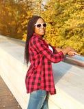 El llevar africano sonriente hermoso de la mujer gafas de sol, camisa a cuadros roja en otoño soleado Fotos de archivo