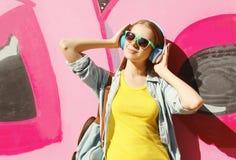 El llevar bastante fresco de la muchacha las gafas de sol, auriculares escucha la música en ciudad Imagenes de archivo