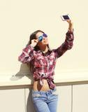 El llevar bonito de la muchacha las gafas de sol y camisa a cuadros hace el autorretrato en el smartphone al aire libre Fotos de archivo