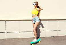 El llevar bonito hermoso de la muchacha gafas de sol y pantalones cortos en el monopatín Fotografía de archivo