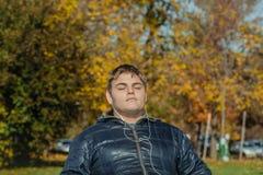 el llevar concentrado del adolescente auriculares y el escuchar la música en parque del otoño en día caliente magnífico soleado Imagen de archivo