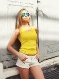 El llevar de la chica joven de la moda gafas de sol y camiseta Imagen de archivo