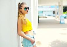 El llevar de la mujer joven de la moda del retrato gafas de sol y camiseta Imagen de archivo