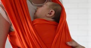 El llevar de la mujer recién nacido en bebé se aferra almacen de video