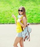 El llevar fresco feliz de la muchacha auriculares, gafas de sol y mochila Fotos de archivo libres de regalías