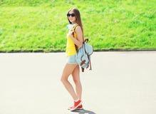 El llevar fresco feliz de la muchacha auriculares, gafas de sol y mochila Fotos de archivo
