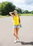 El llevar hermoso de la muchacha gafas de sol y pantalones cortos con la mochila Foto de archivo libre de regalías
