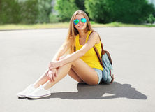 El llevar hermoso de la muchacha gafas de sol y pantalones cortos con la mochila Foto de archivo