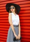 El llevar hermoso de la mujer gafas de sol, sombrero de paja y falda rayada con el embrague del bolso Fotos de archivo