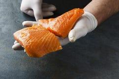 El llevar masculino de las manos kirchen guantes y sostener dos pedazos de salmones frescos contra la tabla oscura fotos de archivo