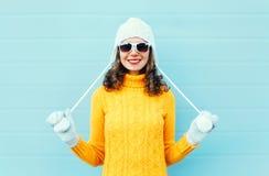 El llevar sonriente joven feliz de la mujer del retrato gafas de sol, sombrero hecho punto, suéter sobre azul Foto de archivo