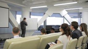 El locutor joven conduce conferencia de funcionamiento en compañía principal metrajes