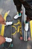 El longboarding patinador de los amigos felices jovenes en un parque de la ciudad Imagen de archivo