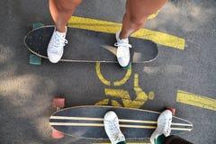 El longboarding patinador de los amigos felices jovenes en un parque de la ciudad Imagen de archivo libre de regalías