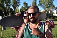 El longboarding patinador de los amigos felices jovenes en un parque de la ciudad Foto de archivo libre de regalías