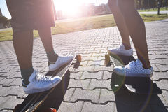 El longboarding patinador de los amigos felices jovenes en un parque de la ciudad Imágenes de archivo libres de regalías