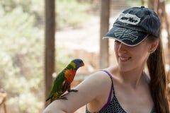 El loro se sienta en la mano de una mujer joven en el parque zoológico australiano Gan Guru en los kibutz Nir David, en Israel Fotografía de archivo libre de regalías