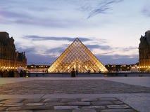 El Louvre - belleza simétrica bajo noche de París imagenes de archivo