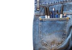 El lápiz y la pluma de la magia en tejanos de un bolsillo en blanco aislaron el fondo Fotos de archivo