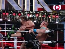 El luchador John Cena de WWE golpea Rusev con el pie en la cara en la esquina de Foto de archivo libre de regalías