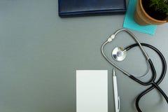El lugar de trabajo del doctor Libreta con la pluma, el estetoscopio y la maceta en un fondo gris fotografía de archivo