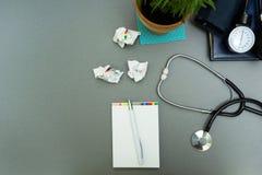 El lugar de trabajo del doctor Libreta con la pluma, el tonometer, el estetoscopio y la maceta en un fondo gris imagen de archivo