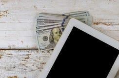 El lugar de trabajo del negocio una tableta y dólares americanos de dinero fotografía de archivo