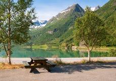 El lugar de vacaciones de viajeros en el banco del lago de la montaña Fotografía de archivo