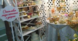 El lujo elegante adornó la barra de caramelo con helar la torta en la fiesta de cumpleaños de oro, concepto de la celebración del almacen de metraje de vídeo