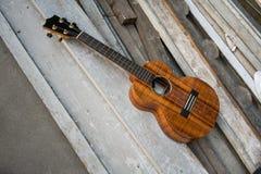El lustre rizado del ukelele del koa acabó contra fondo de madera Fotografía de archivo