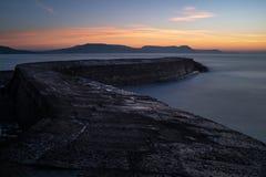 El Lyme Regis Cobb, arrastrando hacia fuera al mar con el sol que sube sobre las colinas distantes, exposición larga imagenes de archivo