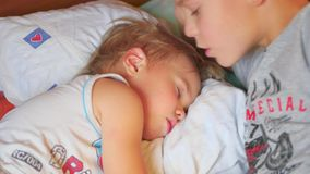 El más viejo hermano besó suavemente al hermano menor durmiente en casa metrajes