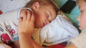 El más viejo hermano frotó ligeramente suavemente al pequeño hermano durmiente en casa metrajes