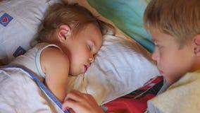 El más viejo hermano frotó ligeramente suavemente al pequeño hermano durmiente en casa almacen de metraje de vídeo
