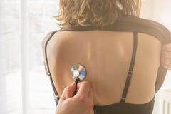 El médico de cabecera escucha los pulmones de una mujer joven con el estetoscopio foto de archivo