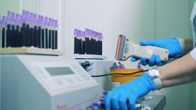 El médico especialista está explorando códigos de barras de tubos de ensayo almacen de metraje de vídeo