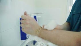 El médico limpia cuidadosamente sus manos con una servilleta sobre el fregadero almacen de metraje de vídeo