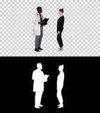 El médico que muestra a un paciente la radiografía resulta entonces las hojas pacientes, Alpha Channel fotos de archivo
