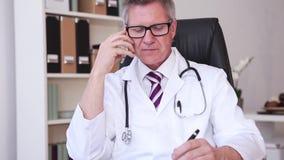 El médico que trabaja con el ordenador portátil en la oficina y escribe almacen de metraje de vídeo