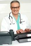 El médico sonriente en ojo desgasta pulsar en el teclado foto de archivo libre de regalías