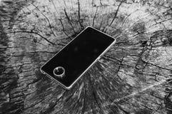El móvil y el anillo se ponen en piso de madera Fotografía de archivo