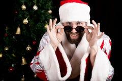 El mún rastoman Santa Claus se sostiene alrededor de los vidrios y de las sonrisas, en el fondo del árbol de navidad diversas emo Fotografía de archivo libre de regalías